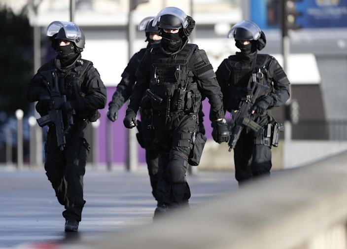 """Members of the French police walk above the """"peripherique"""" (circular road) in Paris, take their positions a kosher grocery store, on January 9, 2015 (AFP Photo/Thomas Samson)"""