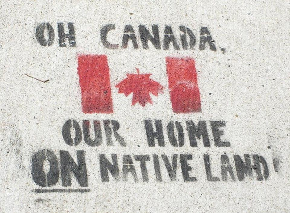 A sign is spray painted on the ground it reads 'Oh Canada, our home ON native land' an upside down Canada flag is also displayed