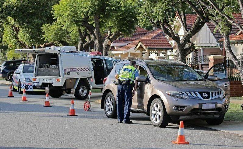 A police major crash officer inspects a four-wheel-drive outside the Inglewood house. Picture:Ben Crabtree/The West Australian.