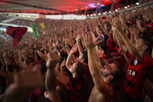 In this April 9, 2014 photo, supporters of the Flamengo soccer team wave their hands during a Copa Libertadores soccer match at Maracana stadium in Rio de Janeiro, Brazil. Soccer's big moment happens in June this year as the best players on the planet meet in Brazil for the World Cup. (AP Photo/Leo Correa)