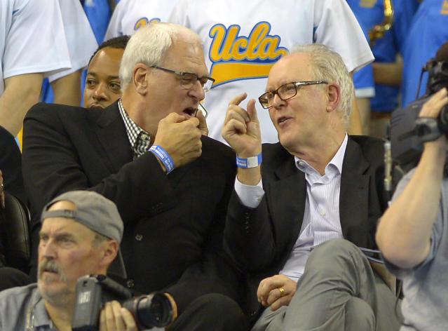 Former NBA coach Phil Jackson, left, and actor John Lithgow talk as they watch UCLA play Arizona during the first half of an NCAA college basketball game on Thursday, Jan. 9, 2014, in Los Angeles. (AP Photo/Mark J. Terrill)