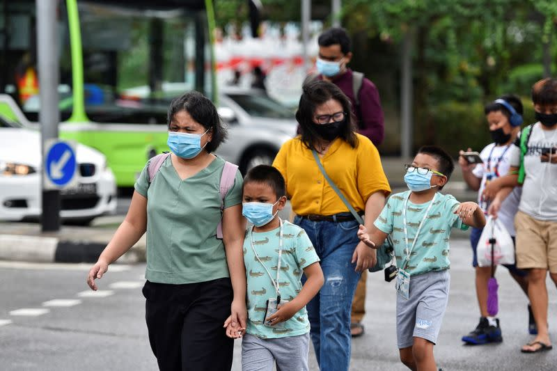 People wearing face masks cross a road amid the coronavirus disease (COVID-19) outbreak in Singapore