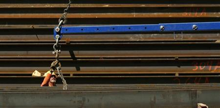 A worker guides a steel beam into place at a construction site in San Francisco