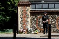 A police officer stands observing minute's silence near to the scene of reported multiple stabbings in Reading
