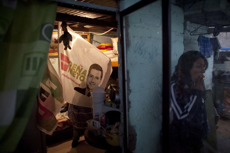 Street vendor Virginia Gutierrez, not seen, shows a flag with an image of presidential candidate Enrique Pena Nieto, of the Institutional Revolutionary Party (PRI) at her home in a impoverished neighborhood in Mexico City, Thursday, June 28, 2012. Mexico will hold its presidential election on Sunday. (AP Photo/Alexandre Meneghini)