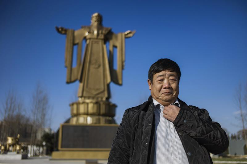 Former general Wang Dianming poses next to a Confucius statue in the seaside resort in Beidaihe, Hebei province, on December 12, 2014 (AFP Photo/Fred Dufour)