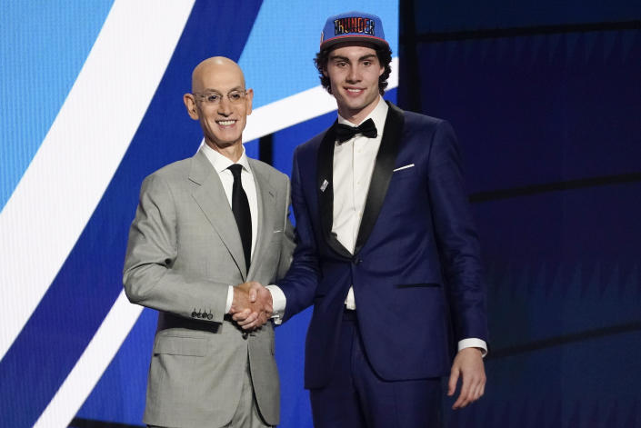 CORRECTS SPELLING TO GIDDEY, INSTEAD OF GIDDY - CORRECTS TEAM TO OKLAHOMA CITY THUNDER, INSTEAD OF GOLDEN STATE WARRIORS - Josh Giddey, right, poses for a photo with NBA Commissioner Adam Silver after being selected sixth overall by the Oklahoma City Thunder during the NBA basketball draft, Thursday, July 29, 2021, in New York. (AP Photo/Corey Sipkin)