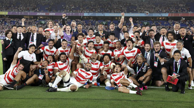 Japan players and management celebrate after defeating Scotland 28-21 in their Rugby World Cup Pool A game at International Stadium in Yokohama, Japan, Sunday, Oct. 13, 2019. (AP Photo/Christophe Ena)