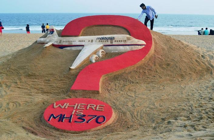 Indian sand artist Sudarsan Pattnaik creats a sand sculpture on missing Malaysia Airlines flight MH370 on Puri beach in eastern Odisha state, on March 7, 2015 (AFP Photo/J .K. Jagdev)