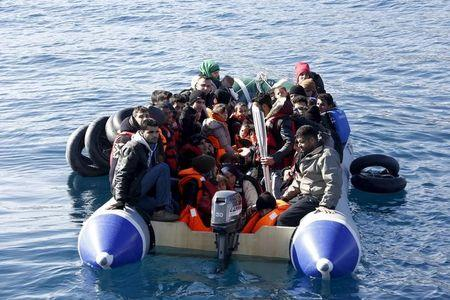 Refugees and migrants are seen on a dinghy as they approach the Ayios Efstratios Coast Guard vessel, during a rescue operation at open sea between the Turkish coast and the Greek island of Lesbos