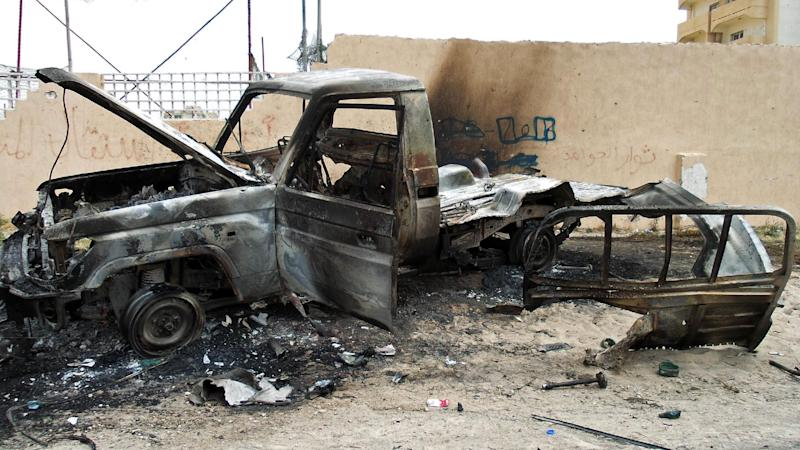 A burnt out vehicle is seen on the side of the road leading to the airport in Tripoli on May 19, 2014 following attacks by armed groups (AFP Photo/Mahmud Turkia)