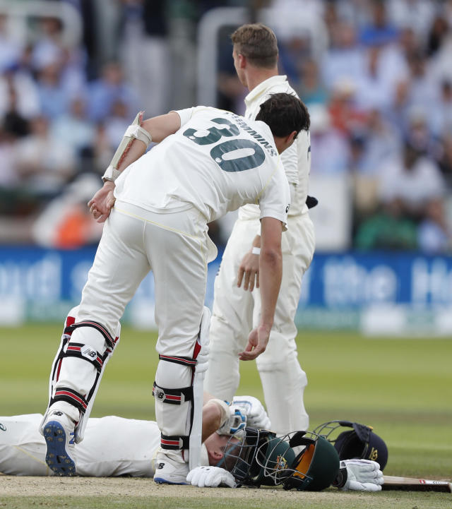 Australia's Steve Smith receives treatment as lies on the ground after being hit on the head by a ball bowled b England's Jofra Archer during play on day four of the 2nd Ashes Test cricket match between England and Australia at Lord's cricket ground in London, Saturday, Aug. 17, 2019. (AP Photo/Alastair Grant)
