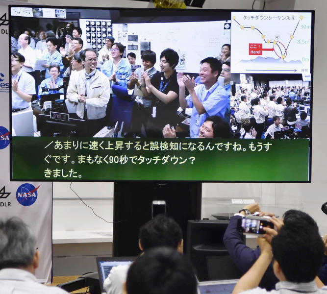 A monitor shows Hayabusa2 project team members celebrating the spacecraft's second touchdown on an asteroid in the control room, at the press center of Japan Aerospace Exploration Agency (JAXA) Sagamihara Campus in Sagamihara, southwest of Tokyo, Thursday, July 11, 2019. Japan's space agency JAXA said Thursday that data transmitted from the spacecraft Hayabusa2 indicated its second successful touchdown on the distant asteroid Ryugu to complete a historic mission - to collect underground samples in hopes of finding clues to the origin of the solar system. (Yu Nakajima/Kyodo News via AP)