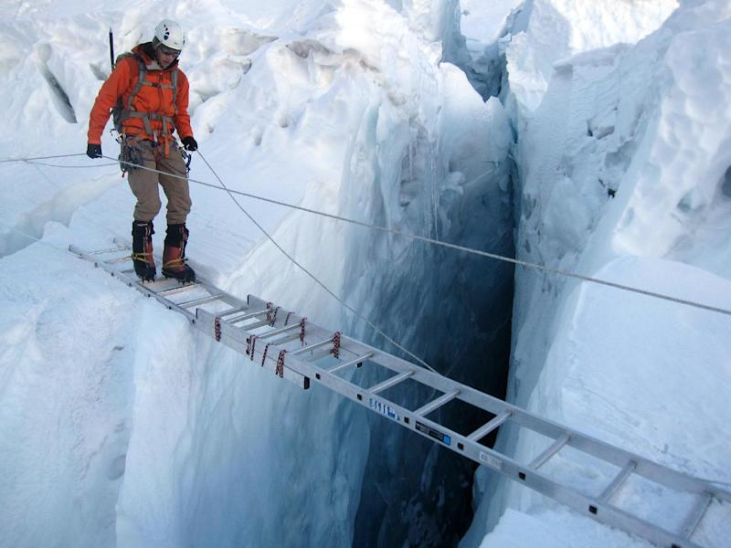 A climber uses a ladder to cross a crevasse on the Khumbu Icefall on Mount Everest on April 16, 2010 (AFP Photo/Adrian Ballinger)