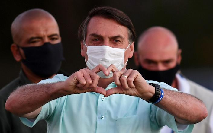 Brazilian President Jair Bolsonaro visits supporters outside Alvorada Palace in Brasilia, on Wednesday. Mr Bolsonaro tested positive in a third test for coronavirus - EVARISTO SA/AFP