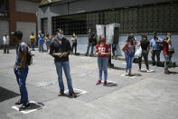 Commuters stand on visual cues to encourage social distancing, as a precaution amid the spread of the new coronavirus, at a bus stop in downtown Caracas, Venezuela, Monday, June 29, 2020. (AP Photo/Matias Delacroix)