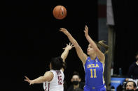 UCLA forward Emily Bessoir (11) shoots over Washington State forward Ula Motuga (15) during the second half of an NCAA college basketball game in Pullman, Wash., Friday, Feb. 5, 2021. (AP Photo/Young Kwak)