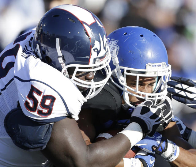 Connecticut defensive tackle Shamar Stephen (59) tackles Buffalo running back Devin Campbell during the first half of an NCAA college football game on Saturday, Sept. 28, 2013, in Buffalo, N.Y. (AP Photo/Mike Groll)