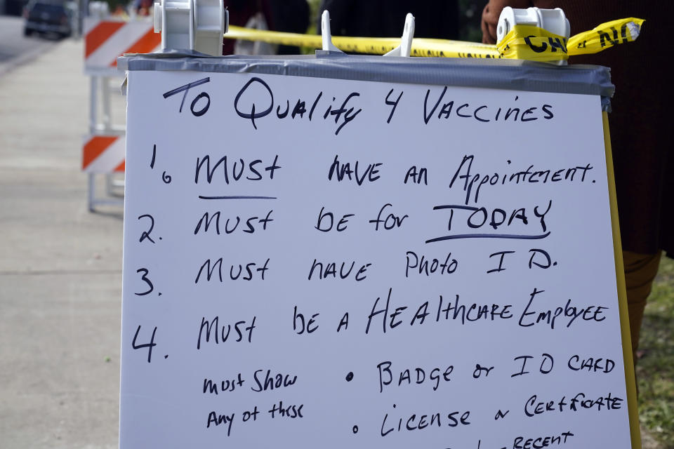 A sign describes the requirements to receive a COVID-19 vaccine at a site for health care workers at Ritchie Valens Recreation Center Wednesday, Jan. 13, 2021, in Pacoima, Calif. (AP Photo/Marcio Jose Sanchez)