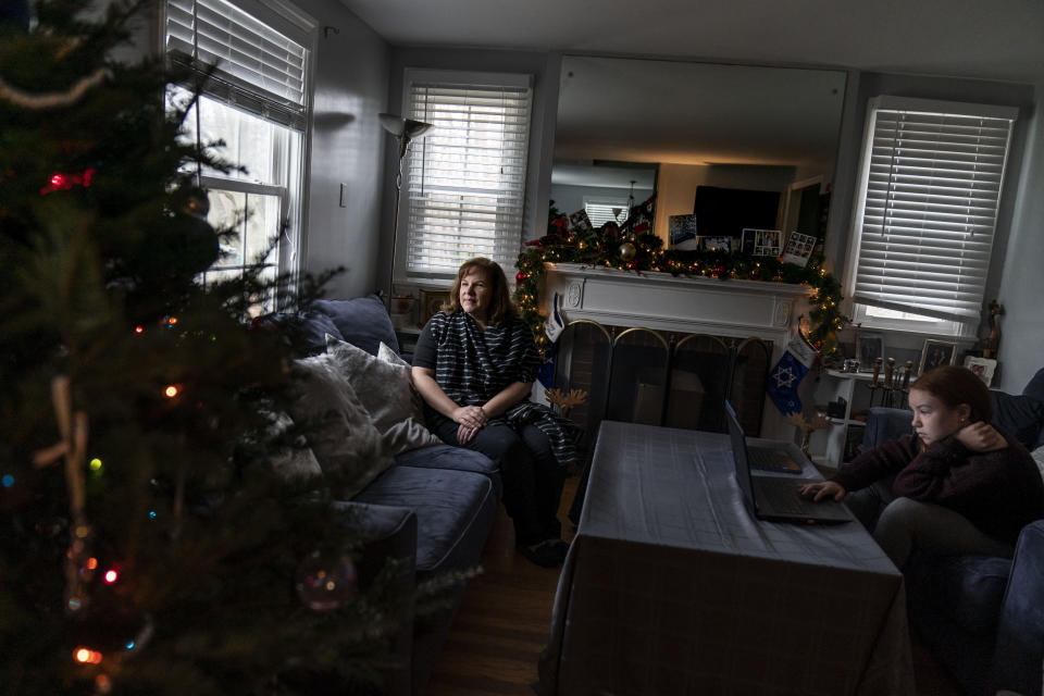 Eileen Carroll, left, sits for a portrait as her daughter, Lily, 11, attends school remotely from their home in Warwick, R.I, Wednesday, Dec. 16, 2020. When Carroll's other daughter tested positive for the coronavirus, state health officials told her to notify anyone her daughter might have been around. Contact tracers, she was told, were simply too overwhelmed to do it. It's the same story across the U.S., as a catastrophic surge in infections has made it difficult or impossible to keep up with the calls considered critical to controlling outbreaks. (AP Photo/David Goldman)