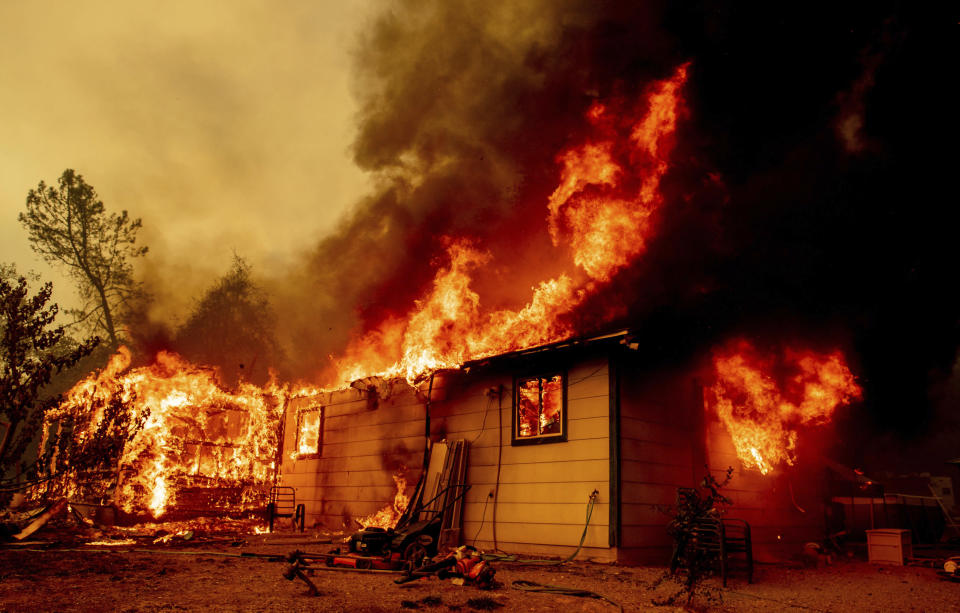FILE — In this Sept. 23, 2021, file photo flames consume a house near Old Oregon Trail as the Fawn Fire burns about 10 miles north of Redding in Shasta County, Calif. Massive wildfires are making it harder for some California homeowners to get property insurance, pitting the state's insurance commissioner, Ricardo Lara, against the industry in an escalating conflict that will likely extend into 2022's statewide elections. Lara, a Democrat, has ordered the pool, the California Fair Access to Insurance Requirements Plan - also known as the FAIR Plan, to sell more than just fire insurance. (AP Photo/Ethan Swope, File)