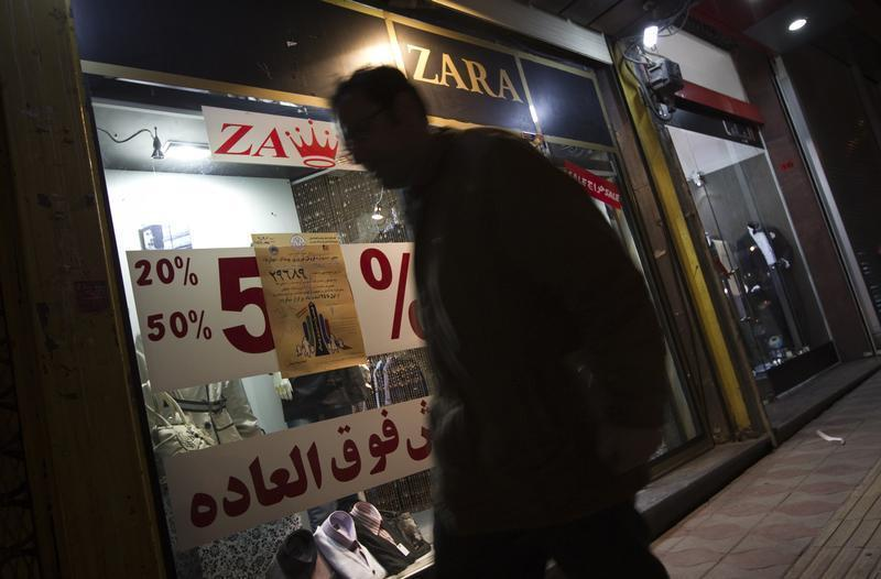 An Iranian man walks past a dress shop in central Tehran