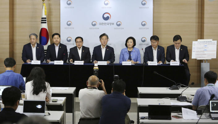 Sung Yun-mo, center, South Korea's minister of Trade, Industry and Energy, speaks during a press conference at the government complex in Seoul, South Korea, Monday, Aug. 5, 2019. Sung said South Korea will spend 7.8 trillion won ($6.5 billion) over the next seven years to develop technologies for industrial materials and parts as it moves to reduce its dependence on Japan during an escalating trade row. The announcement came days after Japan's Cabinet approved the removal of South Korea from a list of countries with preferential trade status. (AP Photo/Ahn Young-joon)