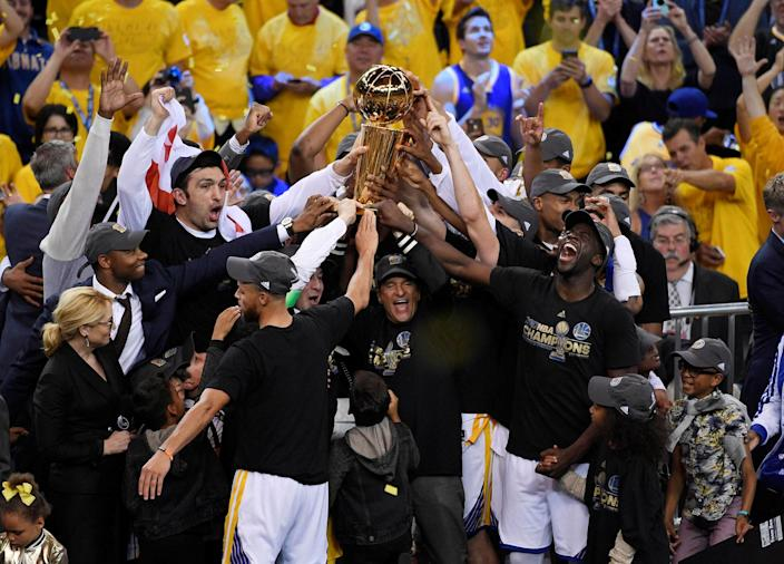 <p>JUN. 12, 2017 – Golden State Warriors players and coaches celebrate with the Larry O'Brien Trophy after defeating the Cleveland Cavaliers in game five of the 2017 NBA Finals at Oracle Arena. (Photo: Kyle Terada-USA TODAY Sports via Reuters) </p>
