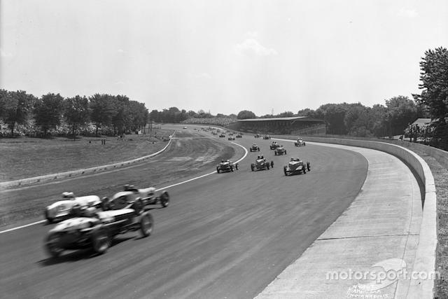 """You can almost 'see' the noise in this great pic taken on the pace lap in 1937. Horn's supercharged Miller (car #3 in the middle of the last row) had been unreliable in practice, and so he took it easy in qualifying, but come the race, he finished third. Note the double wall, and the outer rim of the track now at the same angle as the main surface. <span class=""""copyright"""">IMS Photos</span>"""