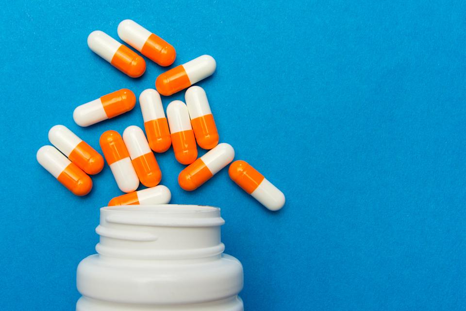 Orange white capsules (pills) were poured from a white bottle on a blue background. Medical background, template.
