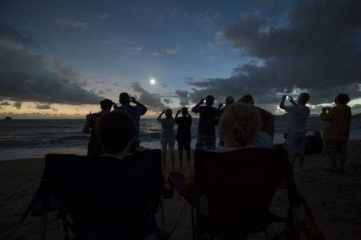 People view the solar eclipse from the beach at Palm Cove in Australia's tropical north Queensland on November 14, 2012. Tens of thousands of sky-gazers flocked to watch the moon block out the sun in one of nature's greatest phenomena -- a total solar eclipse