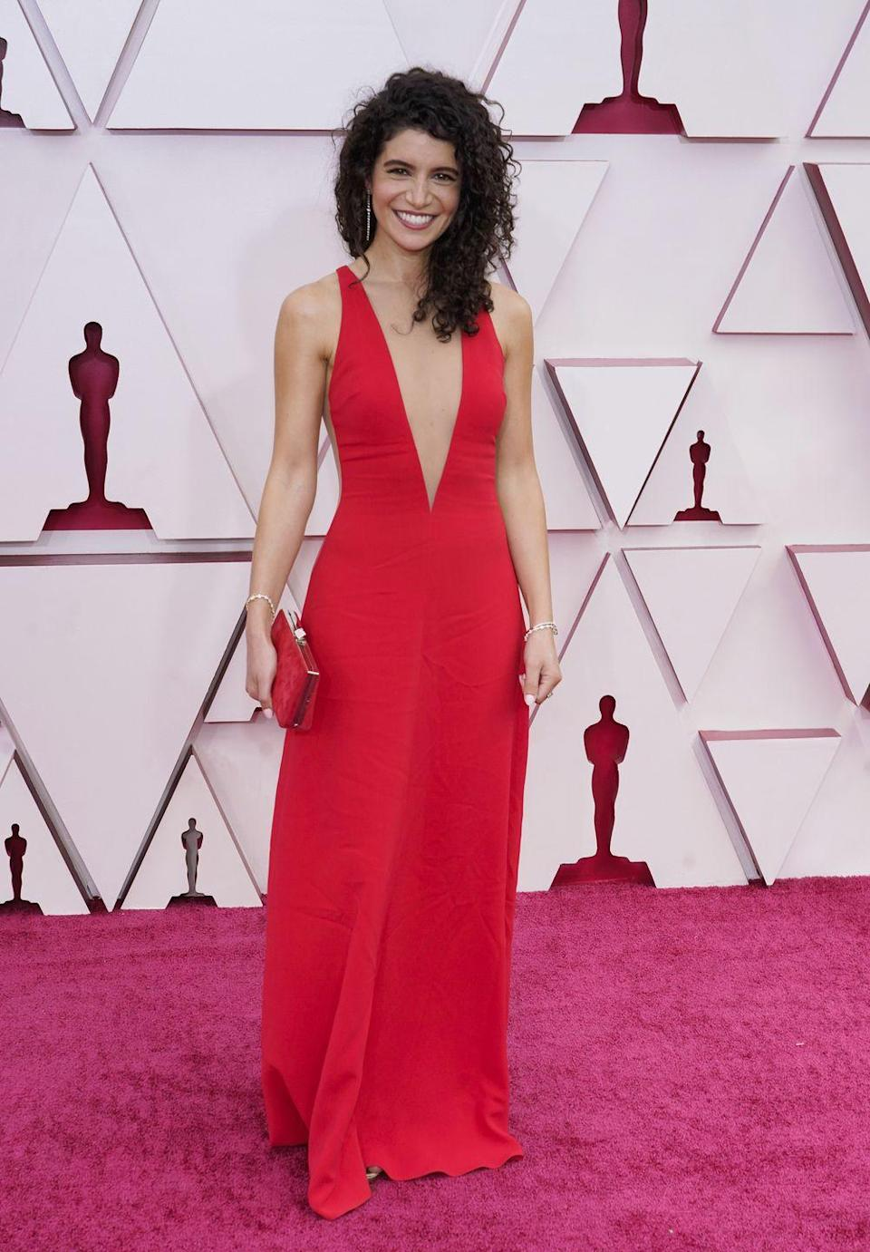 <p>Wearing a simple red sheath with a deep-V. </p>