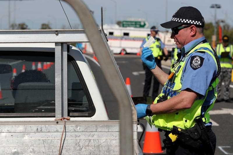 Police officers are seen stopping drivers at an intrastate checkpoint on the Forrest Highway near the border of the Peel and South West regions.
