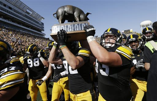 Iowa players carry the Floyd of Rosedale trophy off the field after their 31-13 victory over Minnesota in an NCAA college football game, Saturday, Sept. 29, 2012, in Iowa City, Iowa. (AP Photo/Charlie Neibergall)