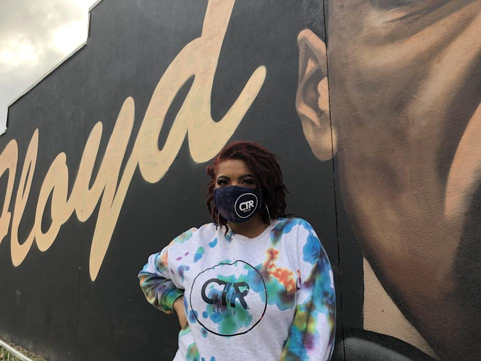 Adriana Holt of Decatur, Ga., stands in front of a mural of George Floyd.