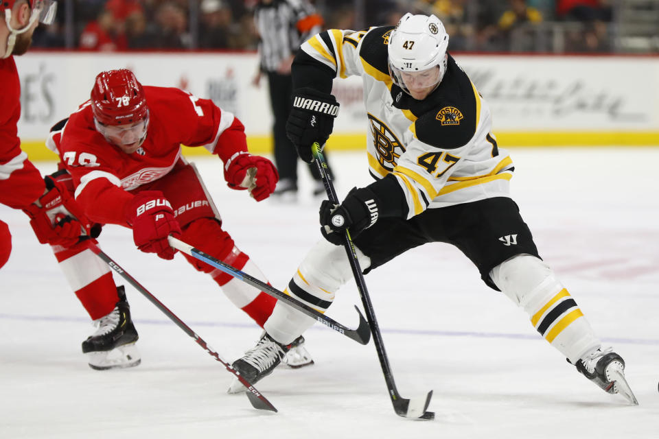 Boston Bruins defenseman Torey Krug (47) protects the puck from Detroit Red Wings center Christoffer Ehn (70) in the first period of an NHL hockey game Sunday, Feb. 9, 2020, in Detroit. (AP Photo/Paul Sancya)