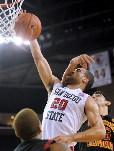 San Diego State forward JJ O'Brien (20) drives to the basket as he tangles with Southern California center Omar Oraby, rear right, during the first half of an NCAA college basketball game, Sunday, Nov. 25, 2012, in Los Angeles. (AP Photo/Gus Ruelas)