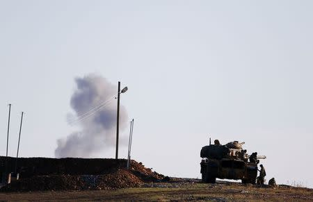 A Turkish army tank drives near the Mursitpinar crossing on the Turkish-Syrian border as smoke rises in the background from the Syrian town of Kobani, October 20, 2014. REUTERS/Kai Pfaffenbach