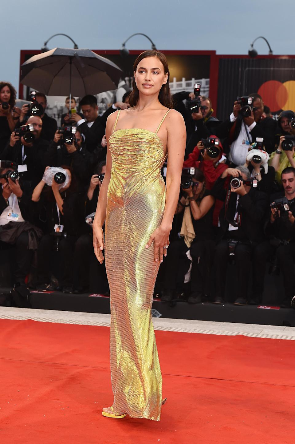 <p>Bradley Cooper's model partner slipped into a gold, shiny Versace dress for the premiere of his film. <em>[Photo: Getty]</em> </p>