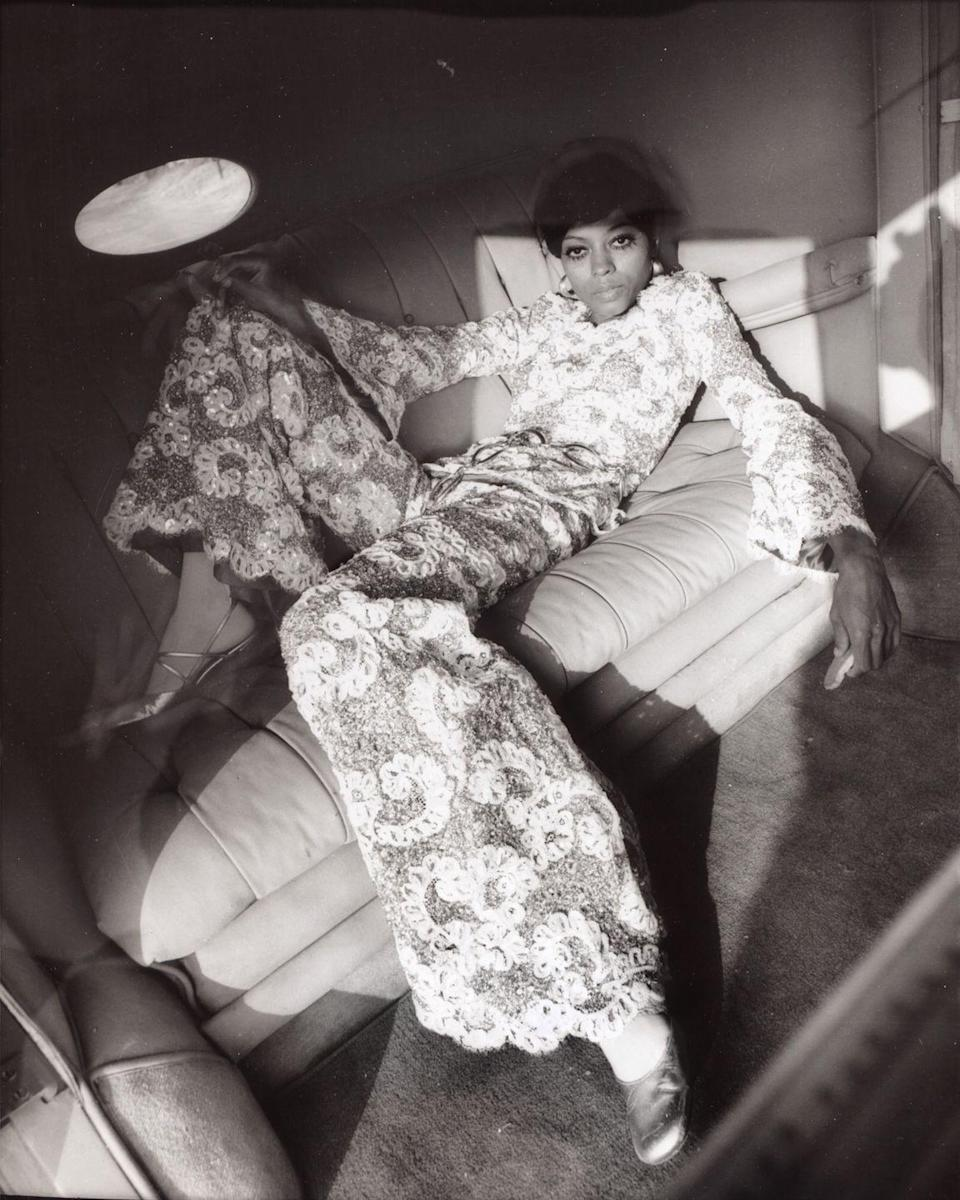 <p>A portrait session gone so right: Ross looks the part of 1970s superstar in a floral and crocheted jumpsuit while lounging on a leather sofa. <br></p>