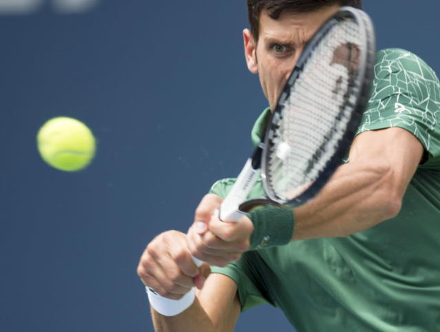 Novak Djokovic, of Serbia, makes a return to Stefanos Tsitsipas, of Greece, during the Rogers Cup men's tennis tournament in Toronto, Thursday, Aug. 9, 2018. (Frank Gunn/The Canadian Press via AP)