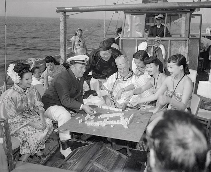 "Robert L. Ripley (seated, in captain's hat) and various guests enjoy a game of mah-jongg aboard the Mon Lei, a junk (type of Chinese sailing ship) he brought across the Pacific from Kowloon, on a cruise on the Long Island Sound in Aug. 1946. Ripley was known for his eponymous show ""Believe it or Not!"" which featured ""unusual"" facts from around the world.<span class=""copyright"">Bettmann Archive—Getty Images</span>"