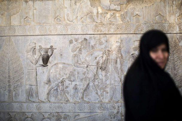 PHOTO: An Iranian woman walks past Achaemenid figuers carved on the wall of the eastern stairway of the Apadana palace at the ruins of Persepolis near Shiraz in Iran on Sept. 26, 2014. (AFP via Getty Images, FILE)