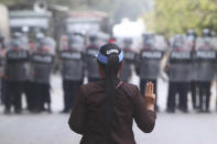A female protester flashes the three-fingered salute in front of police in Mandalay, Myanmar, Saturday, Feb. 20, 2021. Security forces in Myanmar ratcheted up their pressure against anti-coup protesters Saturday, using water cannons, tear gas, slingshots and rubber bullets against demonstrators and striking dock workers in Mandalay, the nation's second-largest city. (AP Photo)
