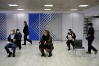 People wait to receive the Moderna vaccine at Promitheas vaccination mega center in Athens, Friday, March 19, 2021. More than 1.35 million doses of the COVID-19 vaccine have been administered so far in Greece, but daily infections remain on the rise despite four months of lockdown measures. (AP Photo/Thanassis Stavrakis)