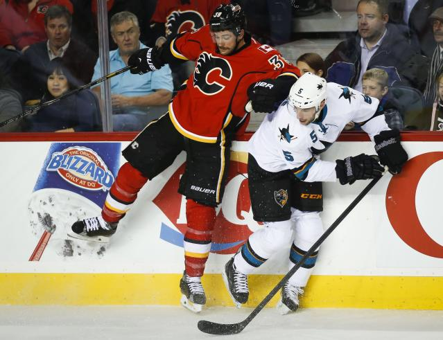 San Jose Sharks' Jason Demers, right, dodges a check from Calgary Flames' TJ Galiardi during the first period of an NHL hockey game Tuesday, Nov. 12, 2013, in Calgary, Alberta. (AP Photo/The Canadian Press, Jeff McIntosh)