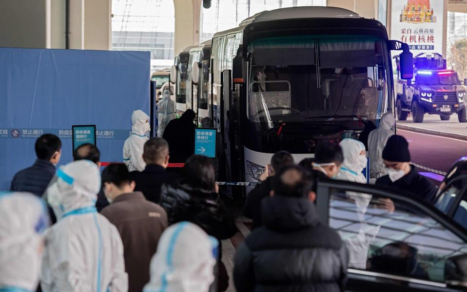 Members of the World Health Organization (WHO) team investigating the origins of the Covid-19 pandemic board a bus - Nicolas Asfouri/AFP