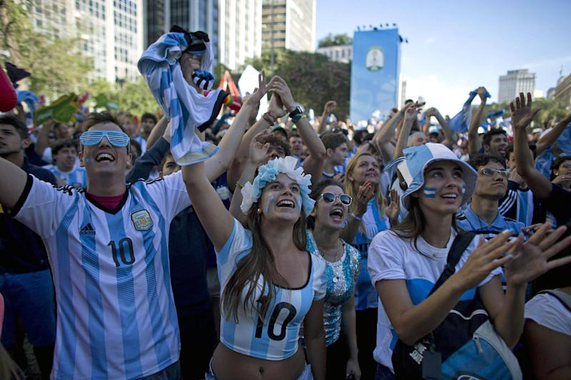 Fans of Argentina celebrate after watching their team score a goal against Switzerland in their World Cup knockout soccer match, at the Fan Fest in Sao Paulo, Brazil, Tuesday, July 1, 2014. Argentina beat Switzerland 1-0 in extra time to reach the quarterfinals