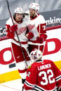 Detroit Red Wings left wing Tyler Bertuzzi, top left, celebrates with right wing Anthony Mantha after scoring a goal as Chicago Blackhawks goalie Kevin Lankinen (32) looks on during the second period of an NHL hockey game in Chicago, Sunday, Jan. 24, 2021. (AP Photo/Nam Y. Huh)