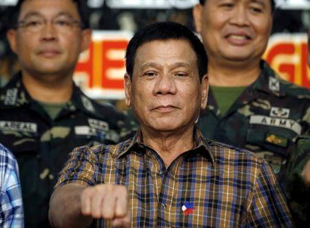 "Philippine President Rodrigo Duterte makes a ""fist bump"", his May presidential elections campaign gesture, with soldiers during a visit at Capinpin military camp in Tanay, Rizal in the Philippines August 24, 2016. REUTERS/Erik De Castro"